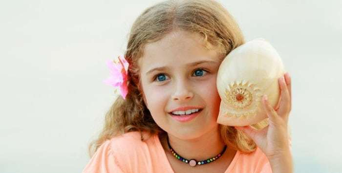 girl-listening-to-sea-shell